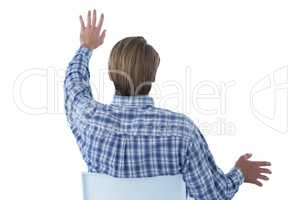 Rear view of businessman using imaginary interface while sitting on chair