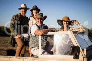 Portrait of happy friends enjoying in vehicle during safari vacation