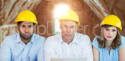 Composite image of portrait of architects wearing hardhats while sitting at table
