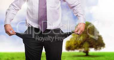 Businessman with empty pockets in nature