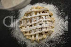 Cropped image of strainer over pie