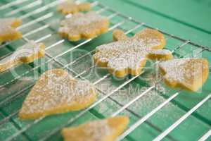 High angle view of powdered sugar on cookies over cooling rack