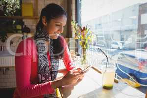 Woman using phone at window sill in cafe