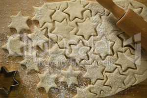 Star shape cookies on dough with rolling pin