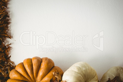 Pumpkins and autumn leaves over white background
