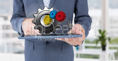 business man holding tablet with 3 d cogs on it