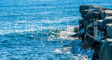 Waves on sunny day splashing against breakwall in shadow.