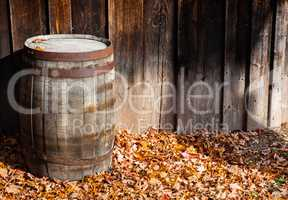 Old wooden cask against wall boards in autumn.