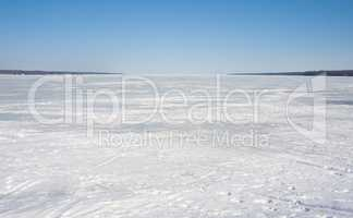 Frozen bay covered in ice under clear blue sky.