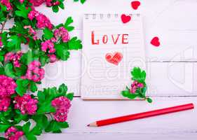 paper notebook with love letter and red heart
