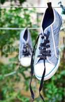 old blue sneaker hanging on a rope behind a wooden clothespin