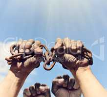 dirty male hands wrapped in a rusty iron chain