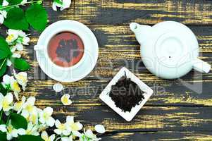 Black tea in a round white cup with saucer