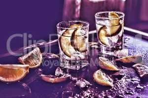 Toned image. Vodka, tequila, gin. Alcoholic cocktail with ice and lime