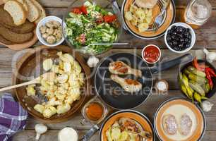 Outdoors Food Concept. Appetizing barbecued chicken legs, chips and a salad of fresh vegetables on a wooden picnic table, top view