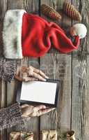 Tablet computer in the human hands. Near the table with tablet computer gift boxes, christmas bell and fluffy fir branches. Free space for text. top view. Copy space.