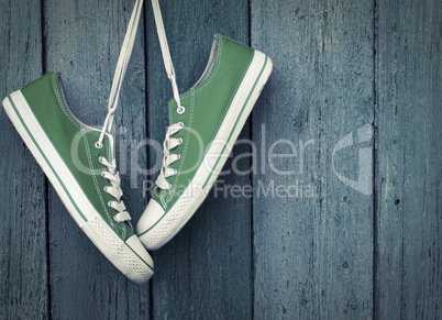 Green youth sneakers hanging on a nail