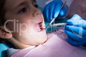 Dentist giving dental treatment to boy at clinic