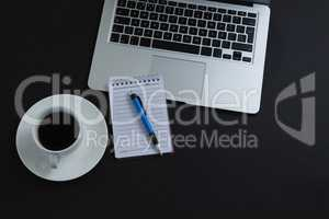 Black coffee, pen, notepad and laptop on black background