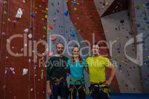 Portrait of athletes standing by climbing wall in health club