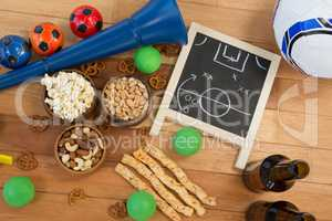 Strategy board, snacks, drink and football on wooden table