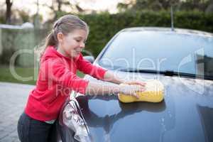 Teenage girl washing a car on a sunny day