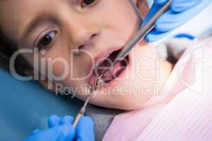 Dentist giving treatment to boy at medical clinic