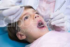 Close up of dentist holding equipment while examining boy