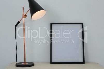 Picture frame and illuminated lamp on table