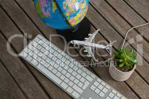 Pot plant, globe, keyboard and airplane model on wooden plank