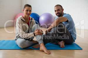 Portrait of student and yoga instructor relaxing in health club