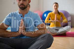 Yoga instructor with student meditating in prayer position at club
