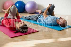 Yoga instructor and student exercising while lying on mat in health club
