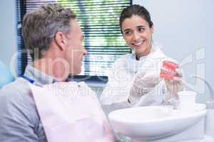 Dentist showing dental mold to man at clinic