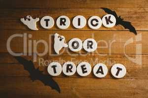 Cookies with trick or treat text by spooky decorations on table