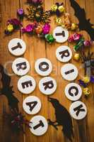 Cookies with trick or treat text by chocolates and decorations on table