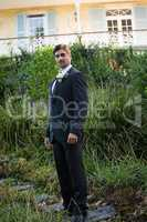 Portrait of handsome bride standing by plants in park