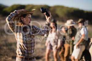 Shocked woman holding binoculars during safari vacation