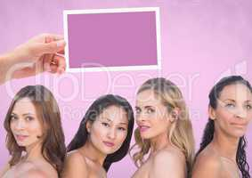 Hand holding card with womens' heads and pink background
