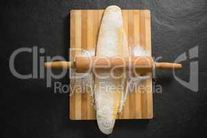 Overhead view of rolling pin on dough over cutting board