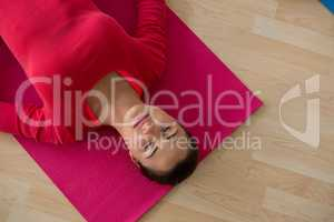 High angle view of woman exercising while lying on mat in yoga studio