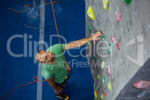 High angle view of male athlete climbing wall in club