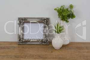 Picture frame and vase on table