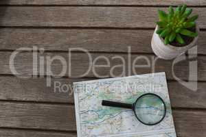 Pot plant, magnifying glass and map on wooden plank