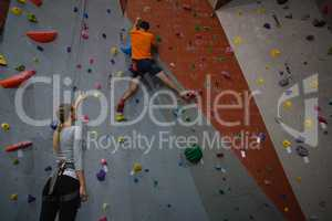 Woman instructing athlete in climbing wall at health club