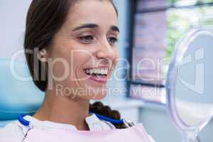Patient smiling while looking at mirror in dental clinic