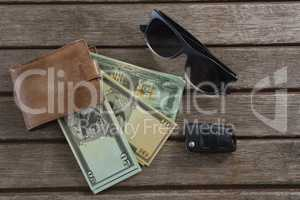 Sunglasses, wallet and currency note on wooden plank