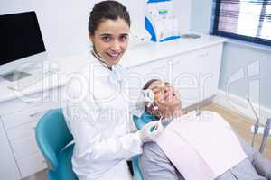 Portrait of dentist holding equipment while standing by patient