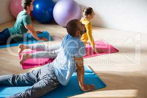 High angle view of yoga instructor with students practicing cobra pose in club