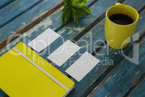 Blank visiting cards, diary, flora and black coffee on wooden plank